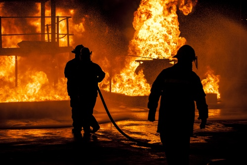 Firefighters approach burning building with hose pipe